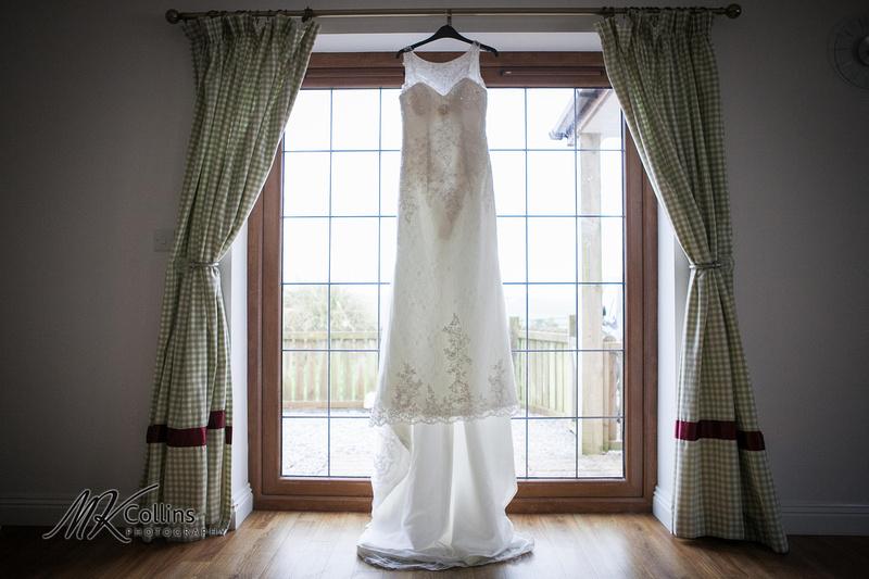 Ocean Kave wedding Wedding Dress hanging by window